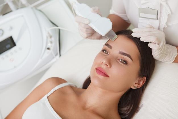 Draufsicht nahaufnahme einer fröhlichen jungen frau lächelnd, während professionelle ultraschallreinigung am schönheitssalon erhalten