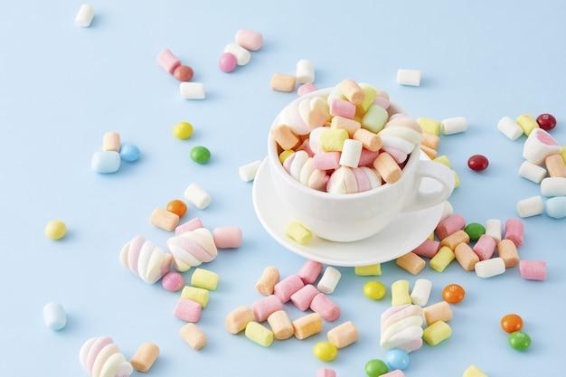 Draufsicht nahaufnahme einer tasse gefüllt mit bunten marshmallows isoliert auf einer blauen oberfläche