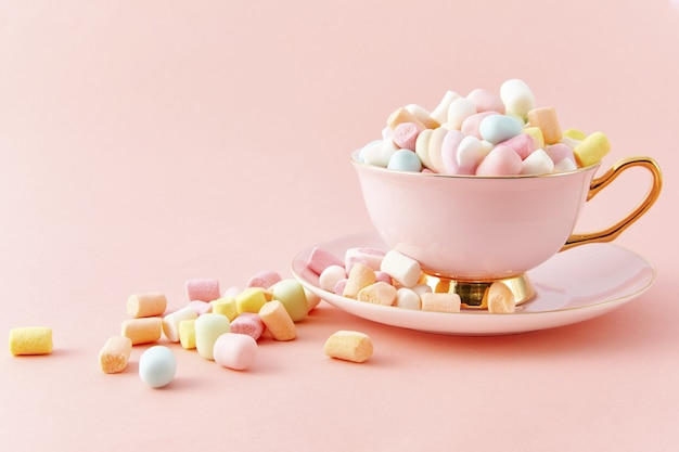 Draufsicht nahaufnahme einer tasse gefüllt mit bunten marshmallows isoliert auf einer rosa oberfläche