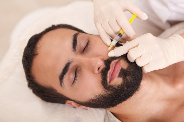 Draufsicht nahaufnahme eines bärtigen mannes, der gesichtsfüller durch kosmetikerin injiziert bekommt