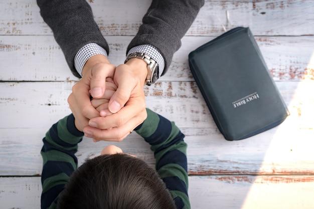 Draufsicht nahaufnahme eines vaters und der hände seines kleinen sohnes, die zusammen nach bibelstudium am morgen beten. christentum, elternschaft und kindererziehung auf gottes weise, dankbarer moment, glücklicher vatertag.
