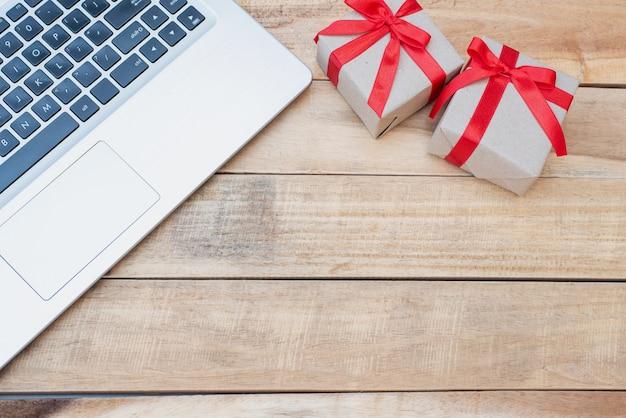 Draufsicht nahaufnahme geschenkboxen und laptop. rote schleife mit geschenkboxen auf holztisch, eingewickelte vintage-box mit kopierraum