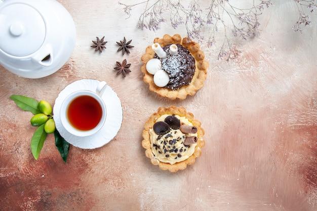 Draufsicht nahaufnahme süßigkeiten zwei cupcakes teekanne eine tasse tee