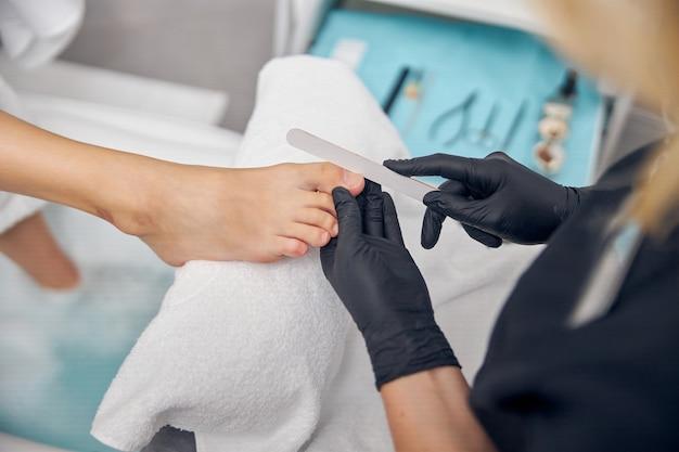 Draufsicht, nahaufnahme von frauenfüßen, da profi nagelfehler für die gestaltung der zehen verwendet