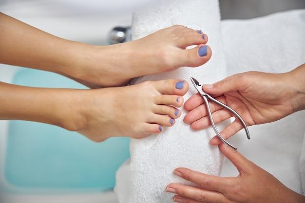 Draufsicht nahaufnahme von weiblichen füßen während der pediküre mit handinstrumenten im spa-salon