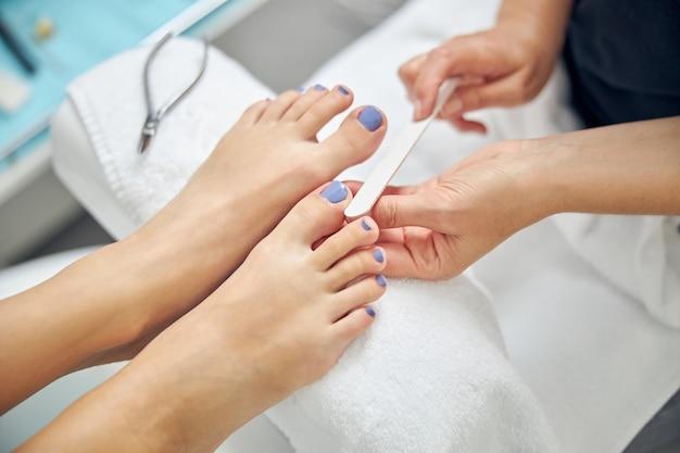 Draufsicht, nahaufnahme von weiblichen füßen während der pediküre mit handinstrumenten im spa-salon