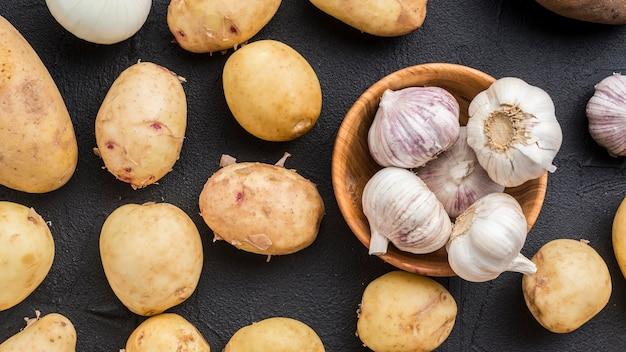 Draufsicht natürliche kartoffeln und knoblauch daneben