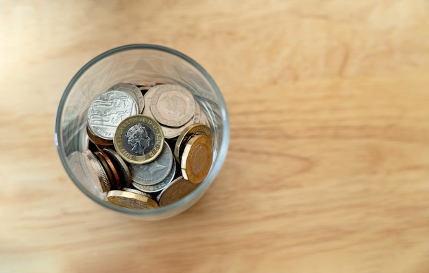 Draufsicht neue britische pfund-münze und penny von einem pfund und in glasflasche auf holztisch