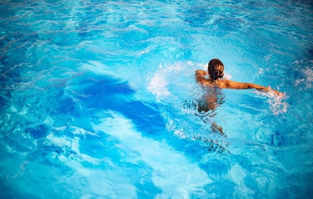 Draufsicht nicht identifiziertes hübsches junges mädchen, das glücklich im blauen klaren wasser im pool unter den strahlen des hellen sonnenlichts spritzt. konzept der entspannung im hotel und auf see. platz für werbung