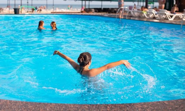 Draufsicht nicht identifiziertes hübsches junges mädchen, das glücklich im blauen klaren wasser im pool unter den strahlen des hellen sonnenlichts spritzt