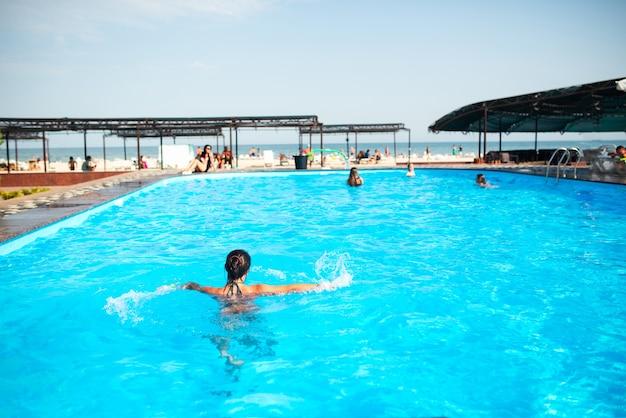 Draufsicht nicht identifiziertes hübsches junges mädchen, das glücklich im blauen wasser im pool unter den strahlen spritzt
