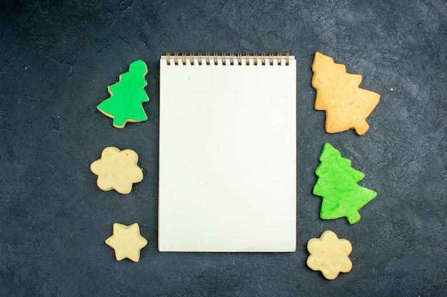 Draufsicht notebook-weihnachtsplätzchen auf dunkler oberfläche