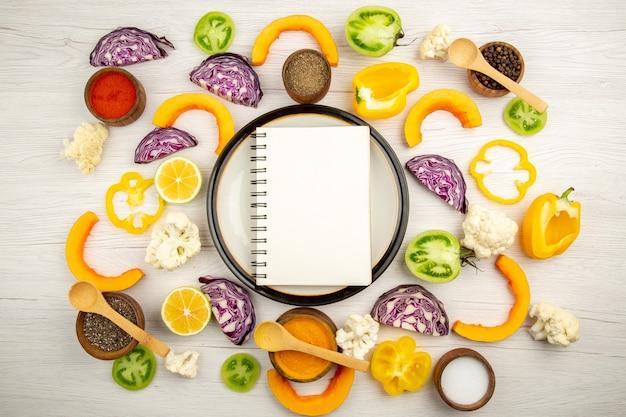 Draufsicht-notizbuch auf runder platte geschnittenes gemüse verschiedene gewürze in kleinen schalen auf weißer holzoberfläche
