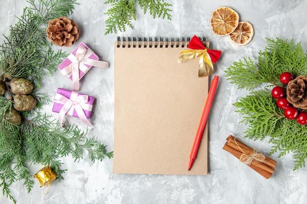 Draufsicht notizbuch bleistift weihnachtsbaum spielzeug kiefer zweige auf grauem hintergrund