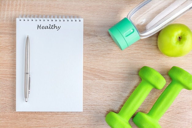 Draufsicht-notizbuch mit text und stift, obst, wasser und sportausrüstung. konzept für einen gesunden lebensstil.