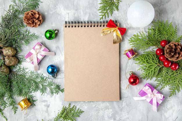Draufsicht notizbuch weihnachtsbaum spielzeug kiefernzweige auf grauem hintergrund