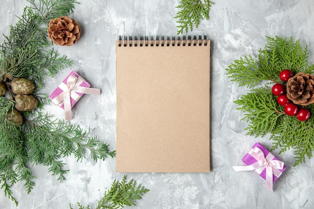 Draufsicht notizbuch weihnachtsbaum spielzeug kiefernzweige auf grauer oberfläche