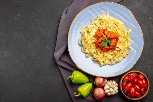Draufsicht nudeln auf tischdecke teller mit appetitlichen nudeln neben der schüssel tomaten knoblauch zwiebel grüner kugelpfeffer auf der lila tischdecke auf dem tisch