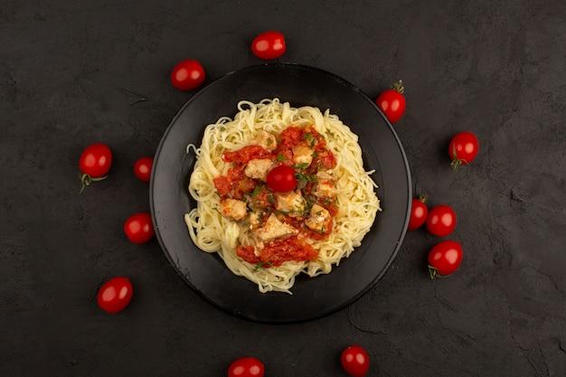 Draufsicht nudeln gekocht mit hühnerflügeln und tomatensauce in schwarzen platte auf dunkel