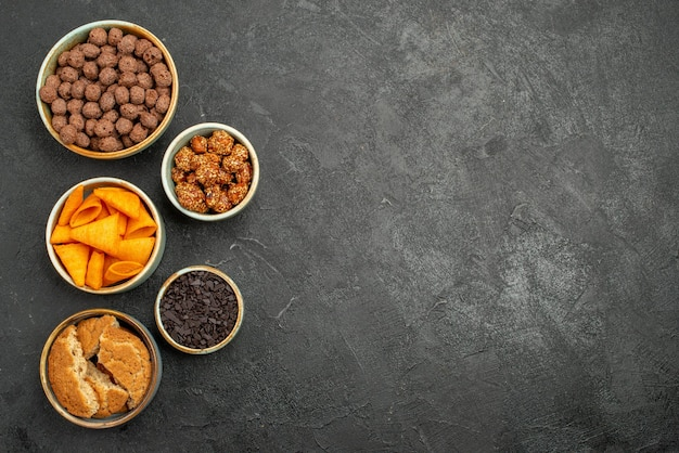 Draufsicht nüsse und chips in kleinen töpfen auf dunkelgrauem snack-chip in schreibtischfarbe