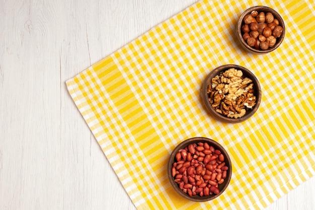 Draufsicht nüsse zusammensetzung frisch geschälte walnüsse erdnüsse und haselnüsse auf weißem schreibtisch nuss viele baumpflanzen snackschale