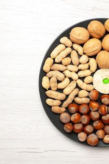Draufsicht nüsse zusammensetzung frische walnüsse erdnüsse und haselnüsse innerhalb der platte auf hellweißem schreibtisch nuss-snack-pflanzenbaum viele schale