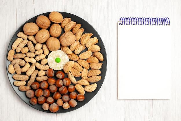 Draufsicht nüsse zusammensetzung frische walnüsse erdnüsse und haselnüsse innerhalb der platte auf weißem schreibtisch nuss snack pflanze baum viele schale