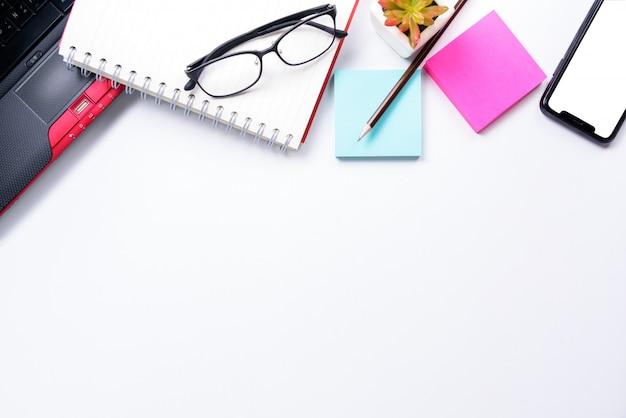 Draufsicht oder flache lageart mit copyspace des arbeitsplatzes mit laptop, stift, notizbuch, brillen, klebriger anmerkung und handy auf weißem tabellenhintergrund