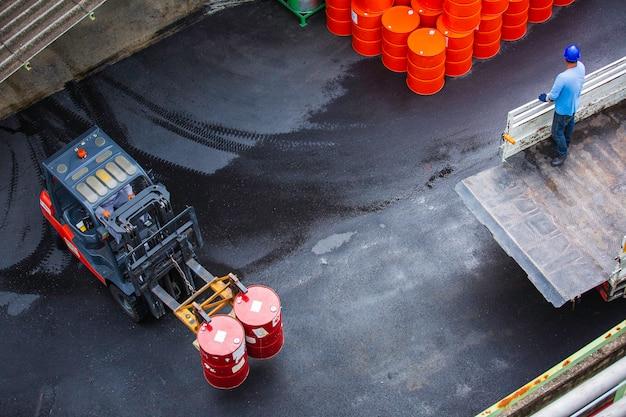 Draufsicht ölfässer gabelstapler bewegen sich auf dem transportwagen männliche arbeiter helfen bei der organisation.