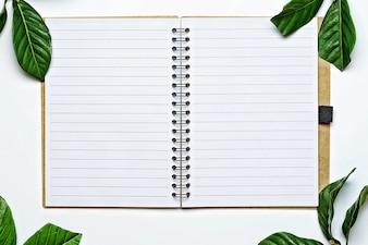 Draufsicht, offenes Notebook mit leeren Seiten auf weißem Schreibtisch.
