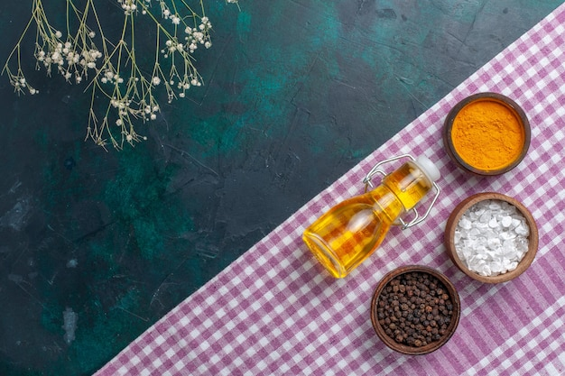 Draufsicht olivenöl mit verschiedenen gewürzen auf dunkelblauem hintergrundbestandteilproduktlebensmittelfoto