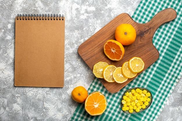 Draufsicht orangen zitronenscheiben auf holzbrett orangen gelbe bonbons in schüssel auf grün-weiß kariertem tischtuch notizblock auf grauem tisch