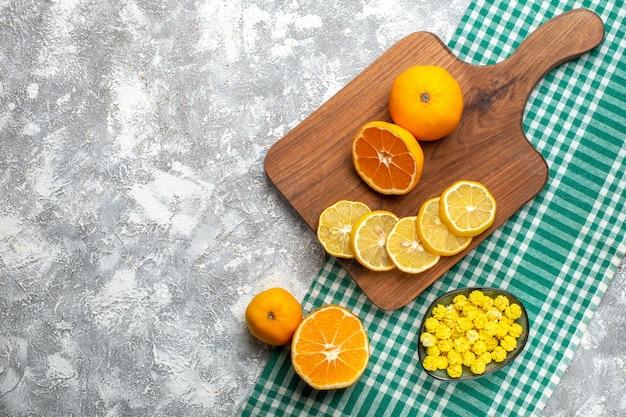Draufsicht orangen zitronenscheiben auf holzbrett zitronen auf grün-weiß karierter tischdecke auf grauem tischfreiraum