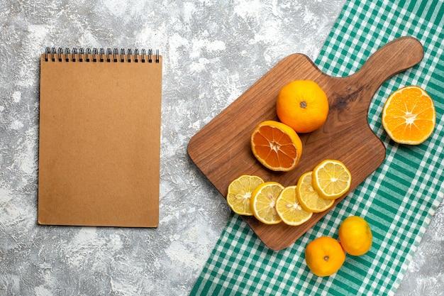 Draufsicht orangen zitronenscheiben auf holzbrett zitronen auf grün-weiß karierter tischdecke notizblock auf grauem tisch