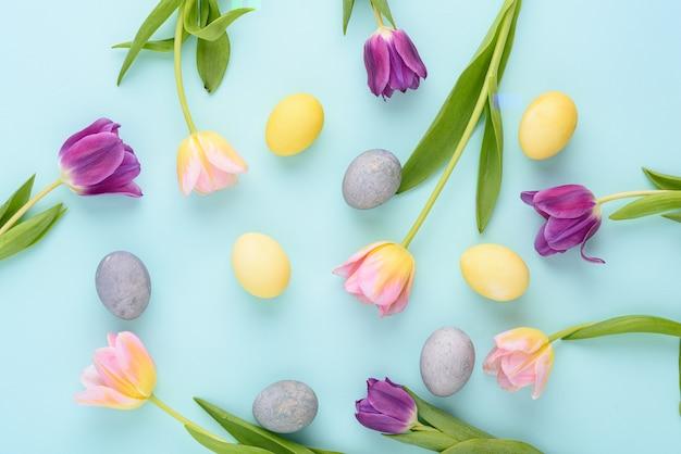 Draufsicht osternhintergrund von lila und rosa tulpen, pastellgelb, blaue eier auf blauem hintergrund, festliches zusammensetzungskonzept