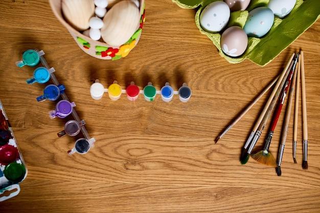 Draufsicht-packung der eier mit pinsel, farbe und dekorativen elementen auf hölzernem hintergrund. kopieren sie platz, frohe ostern, diy, flach legen.