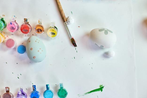Draufsicht-packung von eiern mit pinsel, farbe und dekorativen elementen auf weißem hintergrund. kopieren sie platz, frohe ostern, diy, flach legen.