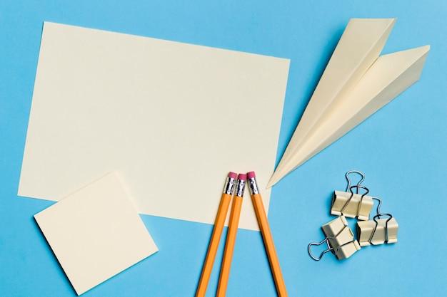 Draufsicht papierflugzeug mit stiften auf dem schreibtisch