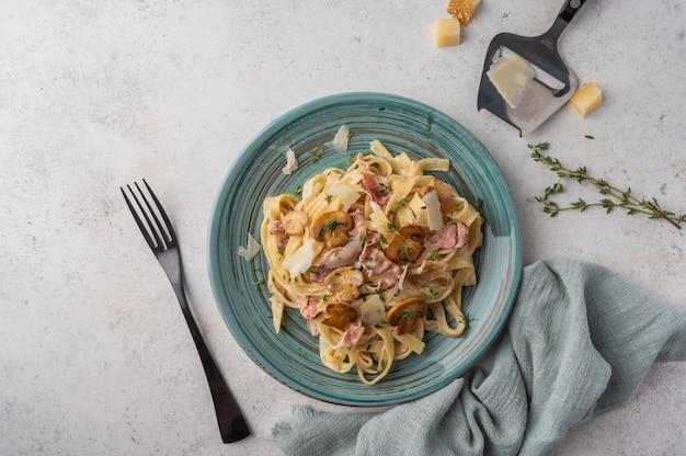 Draufsicht pasta fettuccine mit pilzen, speck, parmesankäse in weißem teller mit gabel