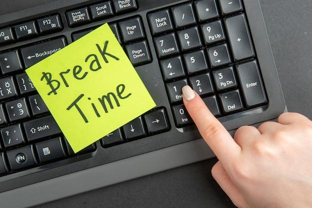 Draufsicht pausenzeit auf haftnotiz auf tastatur weibliche hand auf endtaste auf schwarzer oberfläche geschrieben