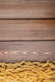 Draufsicht penne pasta auf der unterseite mit kopienraum auf hölzernem hintergrund