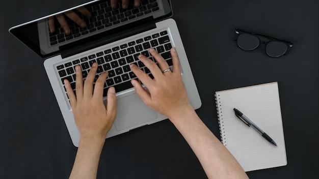 Draufsicht person, die auf laptop mit kopienraum schreibt