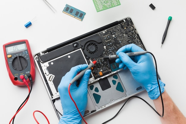 Draufsicht person, die einen laptop repariert