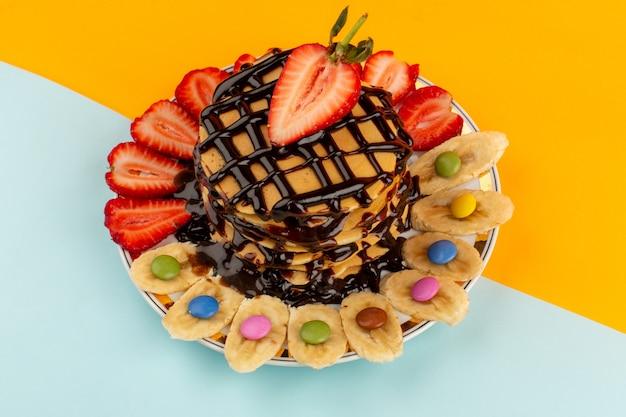 Draufsicht pfannkuchen lecker lecker mit schokolade geschnittenen roten erdbeeren und bananen in teller auf dem farbigen boden