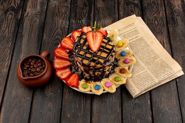 Draufsicht pfannkuchen mit früchten auf dem braunen schreibtisch