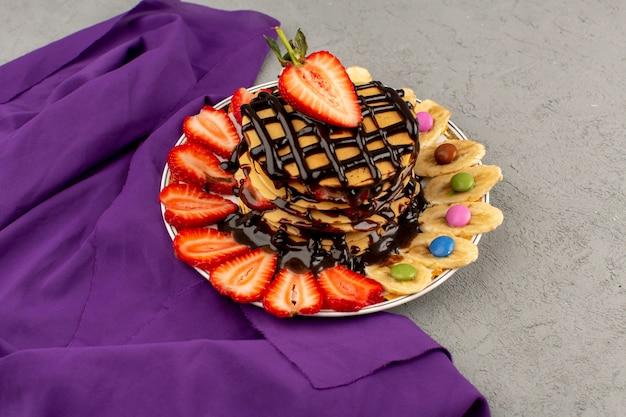 Draufsicht pfannkuchen mit schokoladenrot geschnittenen erdbeeren und bananen in weißer platte auf dem grauen boden