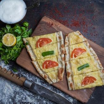 Draufsicht pide mit käse und petersilie und zitrone und ayran im schneidebrett