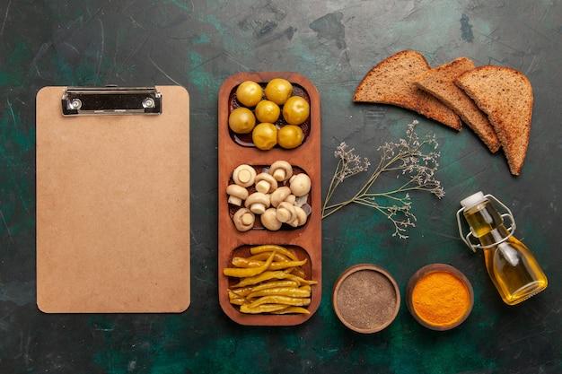 Draufsicht pilze und oliven mit gewürzen und brotlaib auf grünem hintergrund zutatenprodukt mahlzeit essen