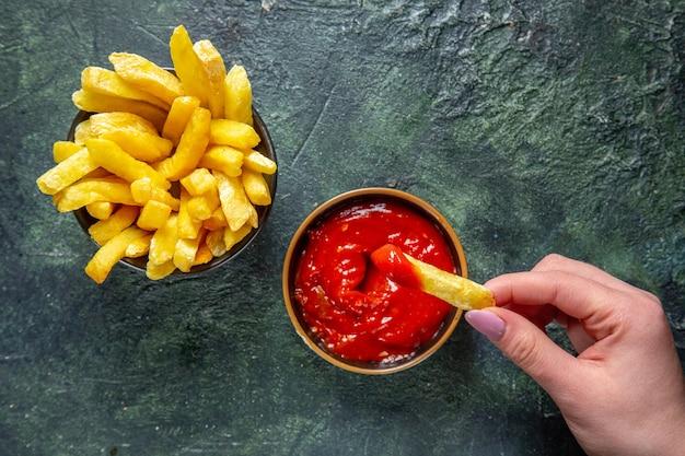Draufsicht pommes frites bekommen essen mit ketchup von frau auf dunkler oberfläche