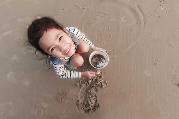Draufsicht portriat asiatisches kleines mädchen, das auf dem sandstrand mit dem abendumgeben spielt